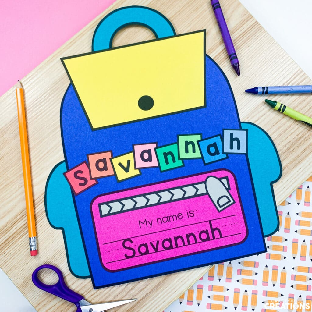 The backpack name writing craft is the perfect back to school activity for any grade level. The craft is pictured with crayons and scissors here.