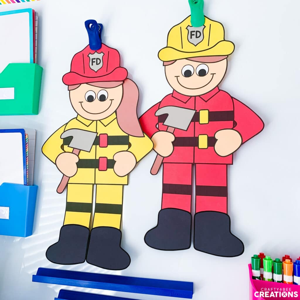 Firefighter crafts hanging up on a whiteboard by clips.
